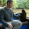 Sitting in a boat and feeding a banana to a wooley monkey