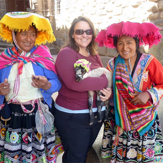 Kim holding a lamb and posing with Andean women