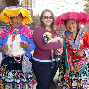 Kim holding a lamb and posing with two Andean women